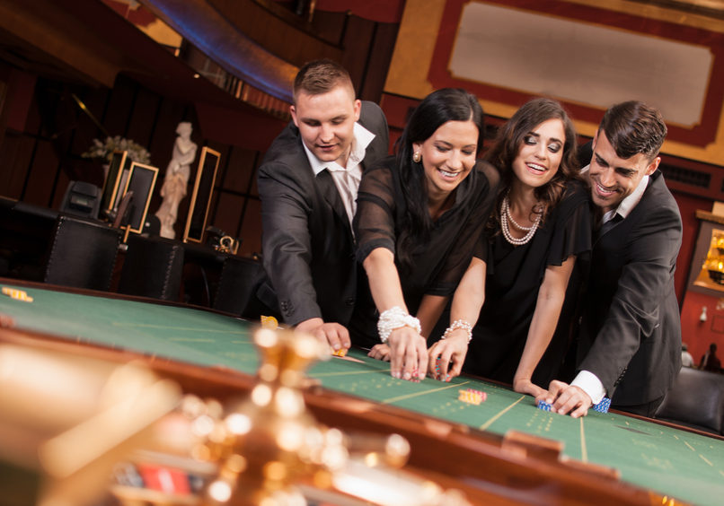 Four people playing roulette in casino.