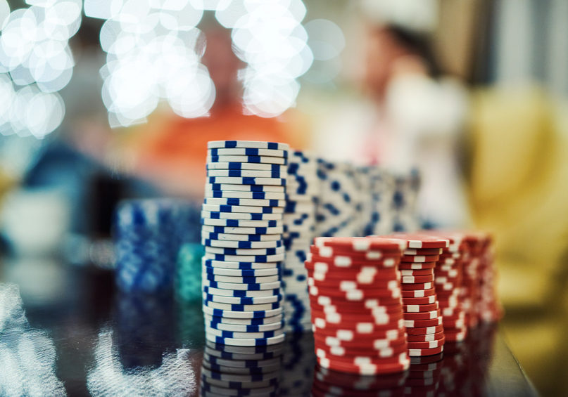 red and blue poker chips on the table, defocused lights in background, leisure games.